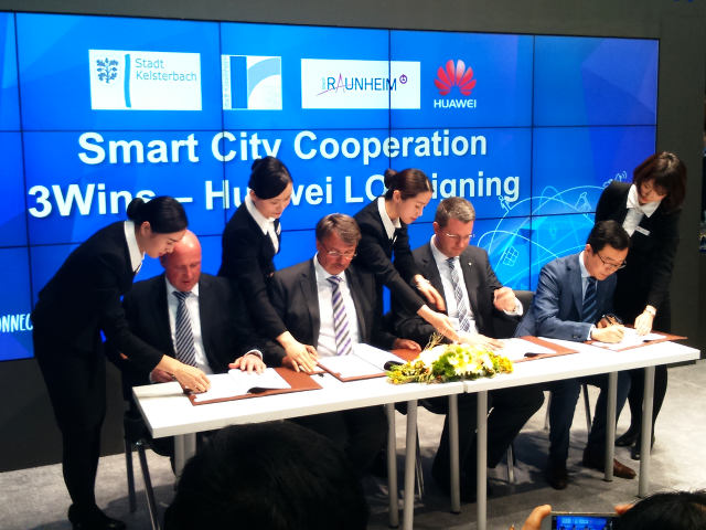 Majors signing the agreement. A big display show the text: Smart City Cooperation 3Wins - Huawei LOI Signing